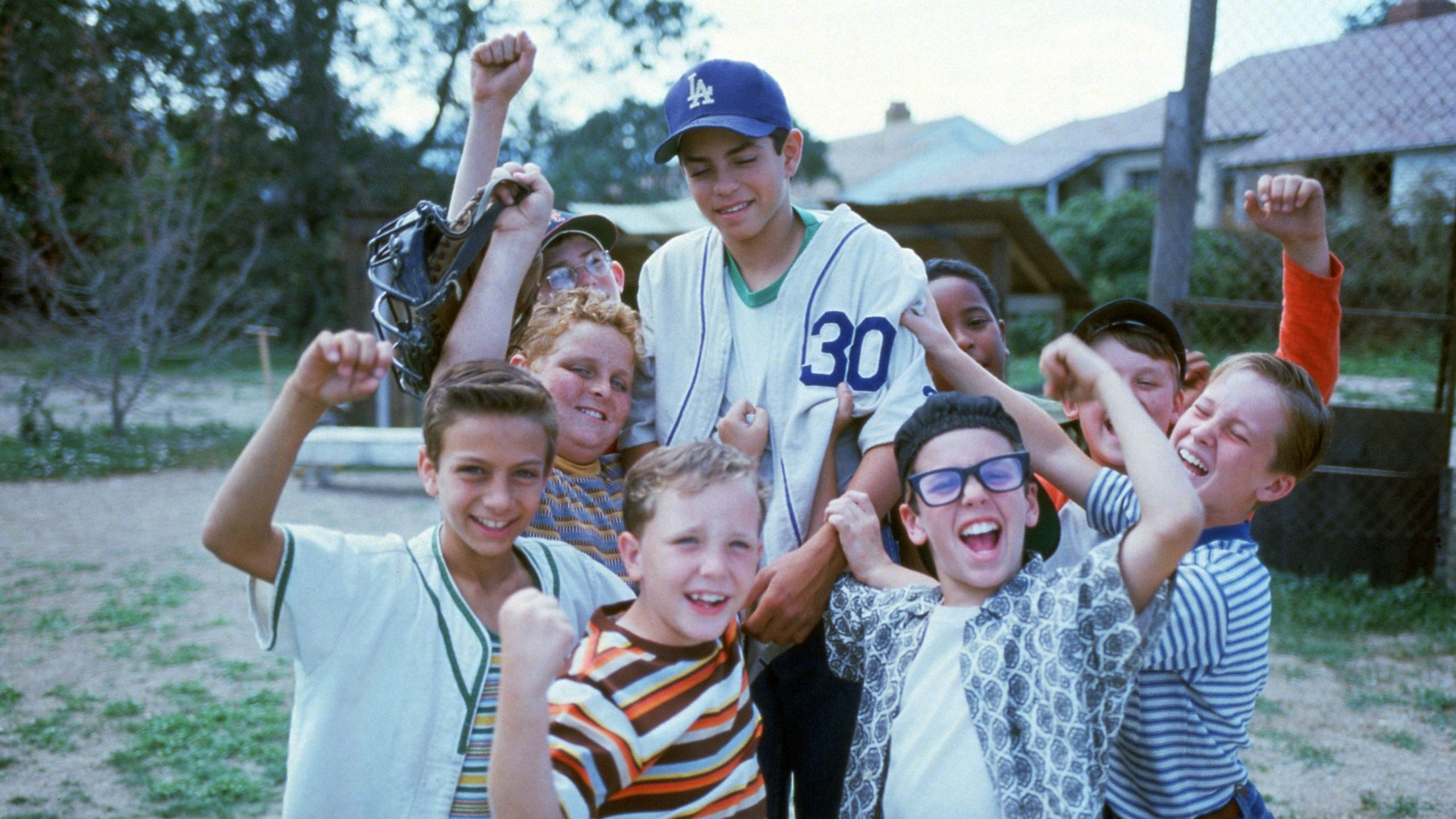 The cast of The Sandlot cheering with Ben Rodriguez on their shoulders.