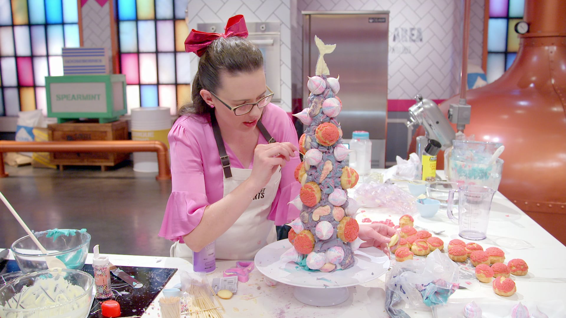 A contestant creating a macaroon tower in season 2 of Zumbo's Just Desserts [ a food based palate cleanser].