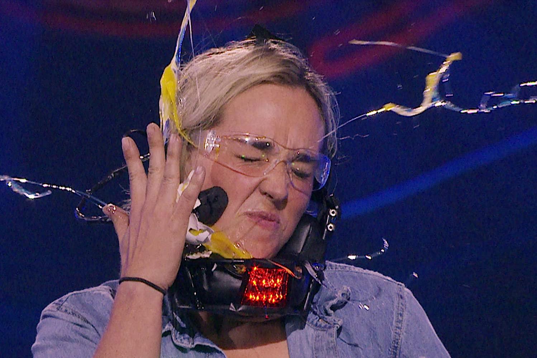 A woman smashing an egg into her face on Awake.