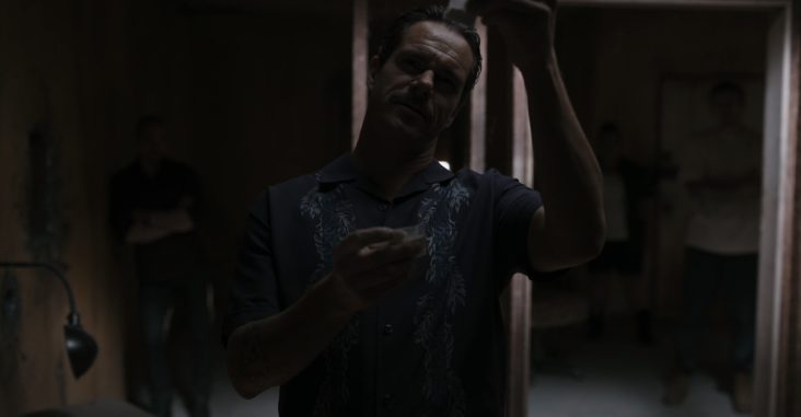 Lalo examines small bags of drugs.