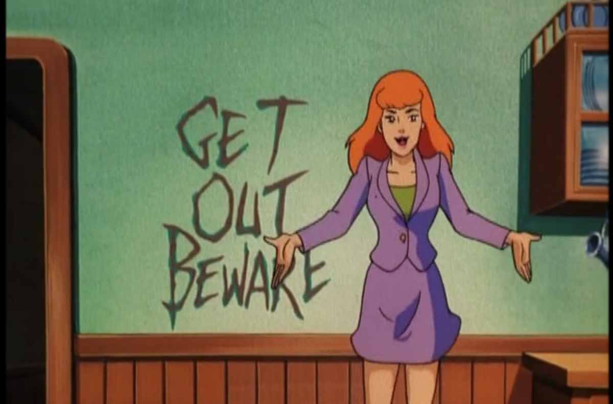 "Daphne in front of a wall with the carved out words ""get out beware."""