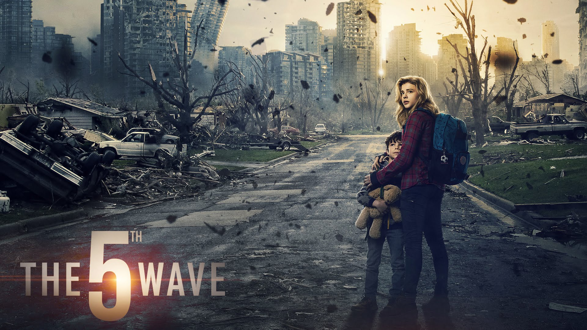 The main characters, a teenage girl and her younger brother, embrace in the midst of a decimated city filled with debris in the movie adaptation of the YA novel The 5th Wave.