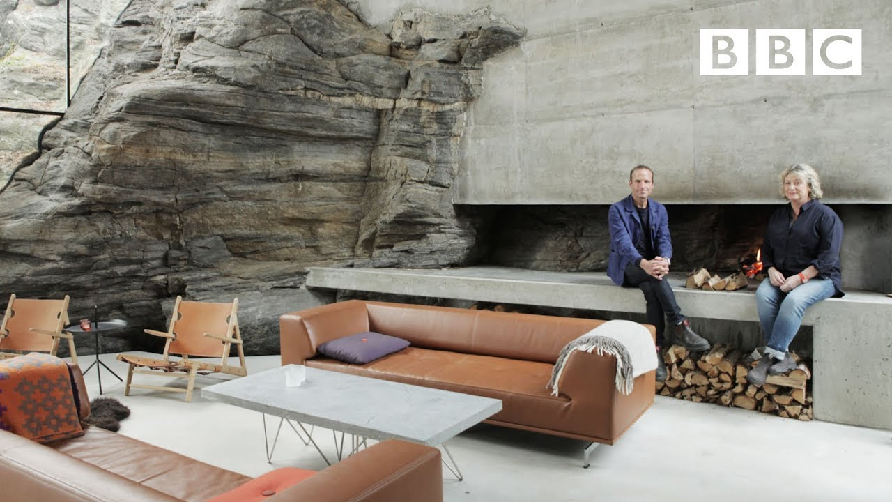 Piers Taylor and Caroline Quentin perch on a fireplace in one of the featured extraordinary homes of the lifestyle palate cleanser, The World's Most Extraordinary Homes.
