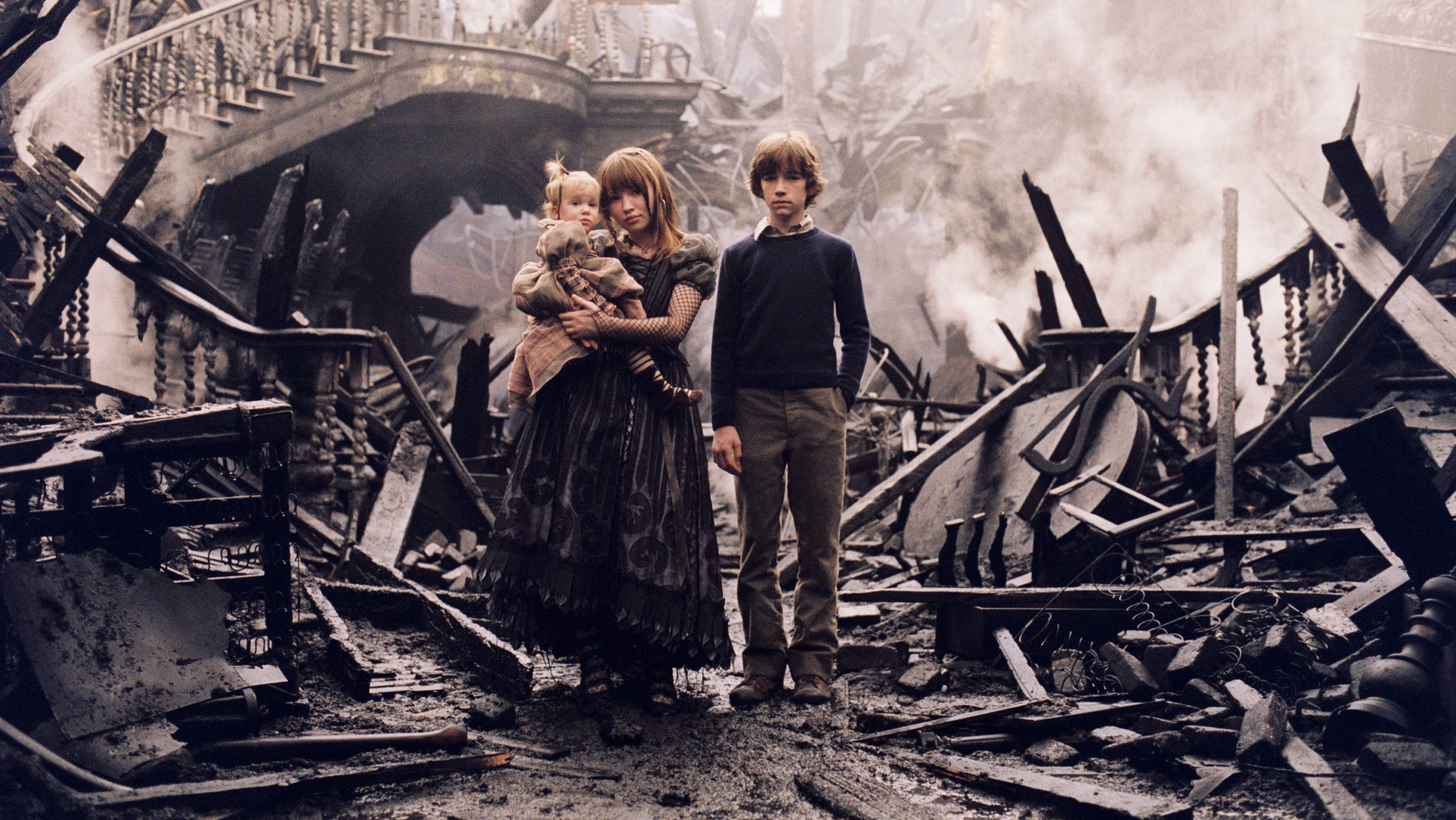 The three Baudelaire siblings standing in the burnt ruins of their former home.