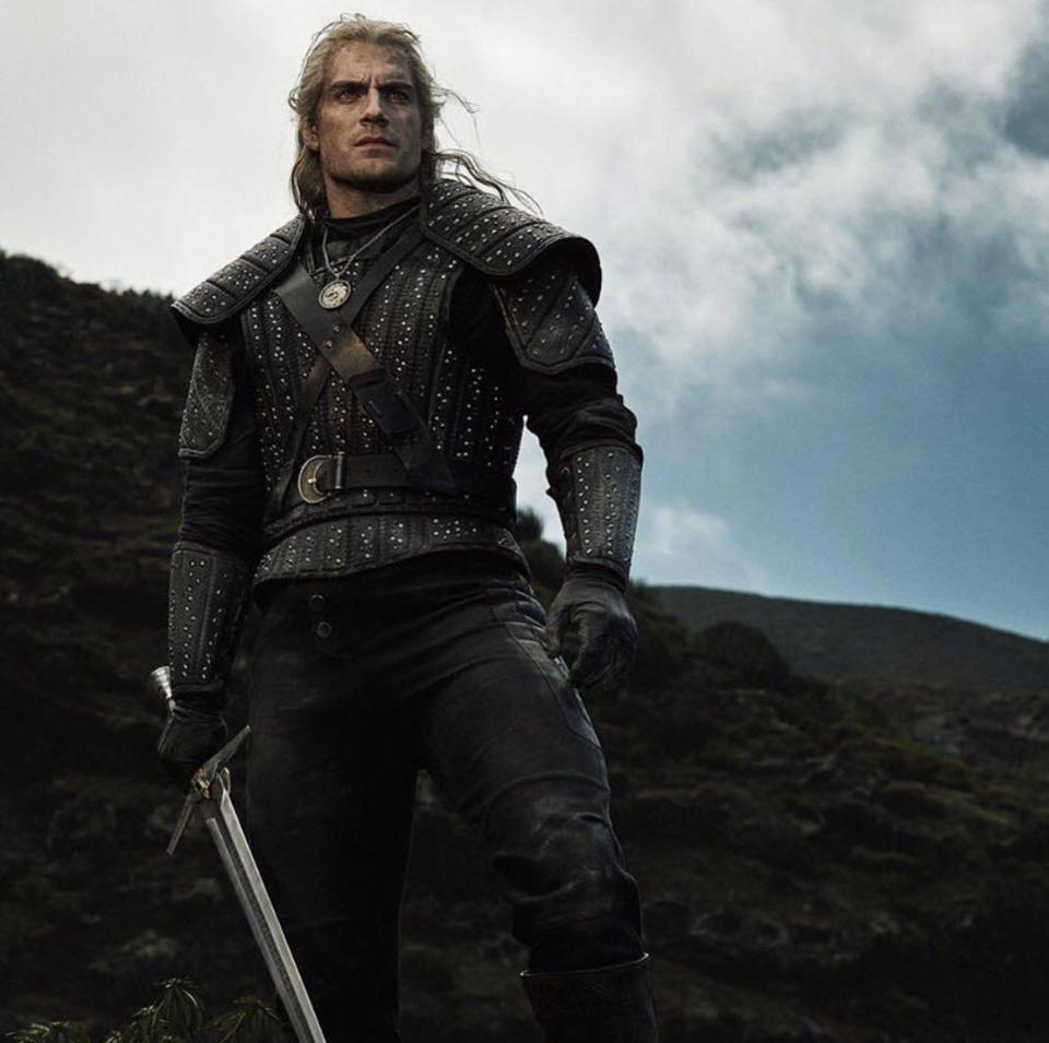 Henry Cavill as Geralt of Rivia in the Netflix adaptation of The Witcher standing on a hillside staring into the distance.