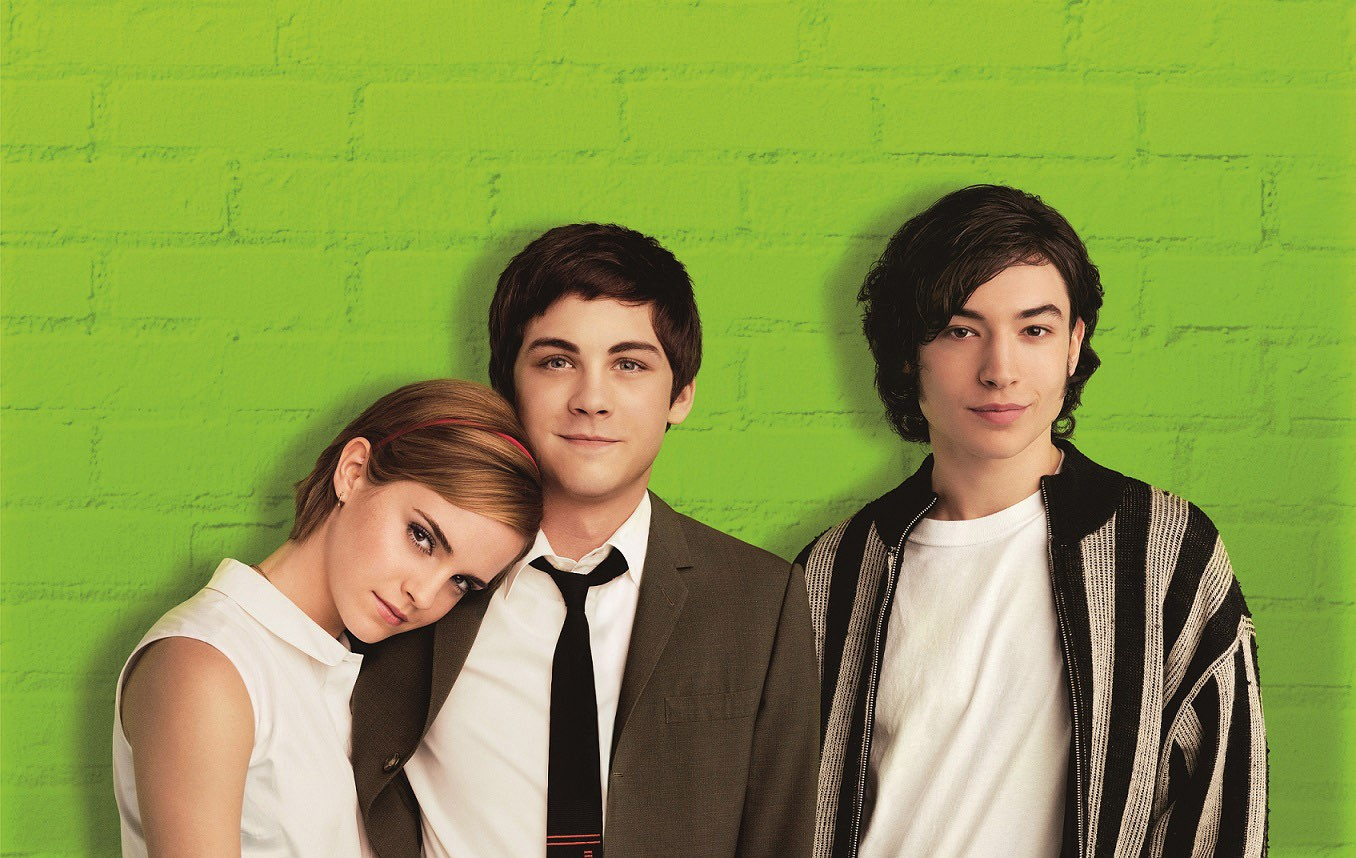 Teenage main characters Charlie, Sam, and Patrick pose against a neon green brick wall.