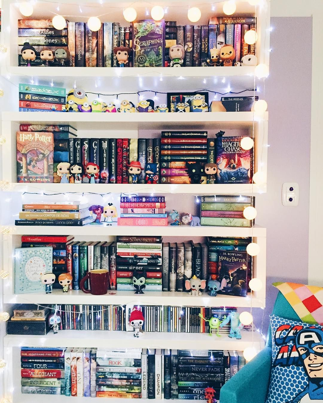 A white book case filled with colorful books and decorations surrounded by string lights.