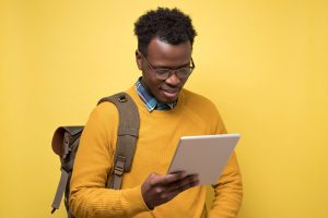 Man in yellow reading on tablet