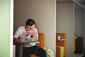 Stressed employee works at laptop