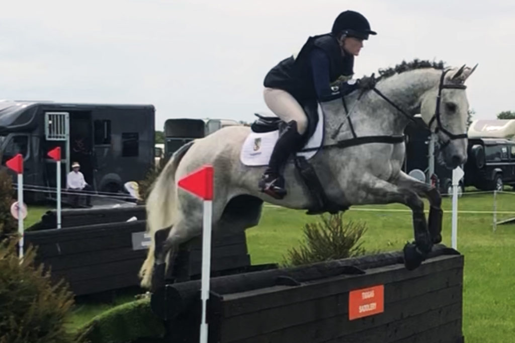 Grey horse jumping cross country fence