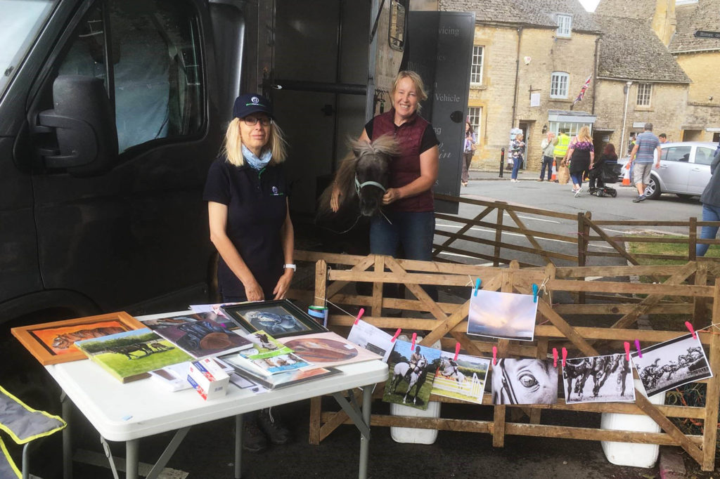 Two ladies with chestnut pony standing in front of a horse box by a table with pictures of horses