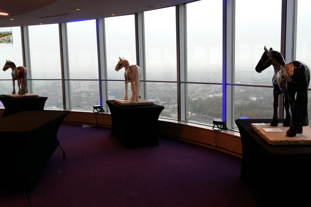 Painted horse sculptures stood in front of tall glass windows looking out over London