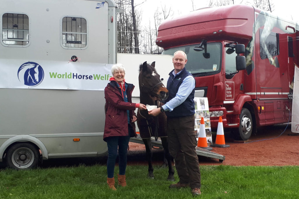 Lady giving a cheque to a man wearing a World Horse Welfare waistcoat who is holding a bay pony