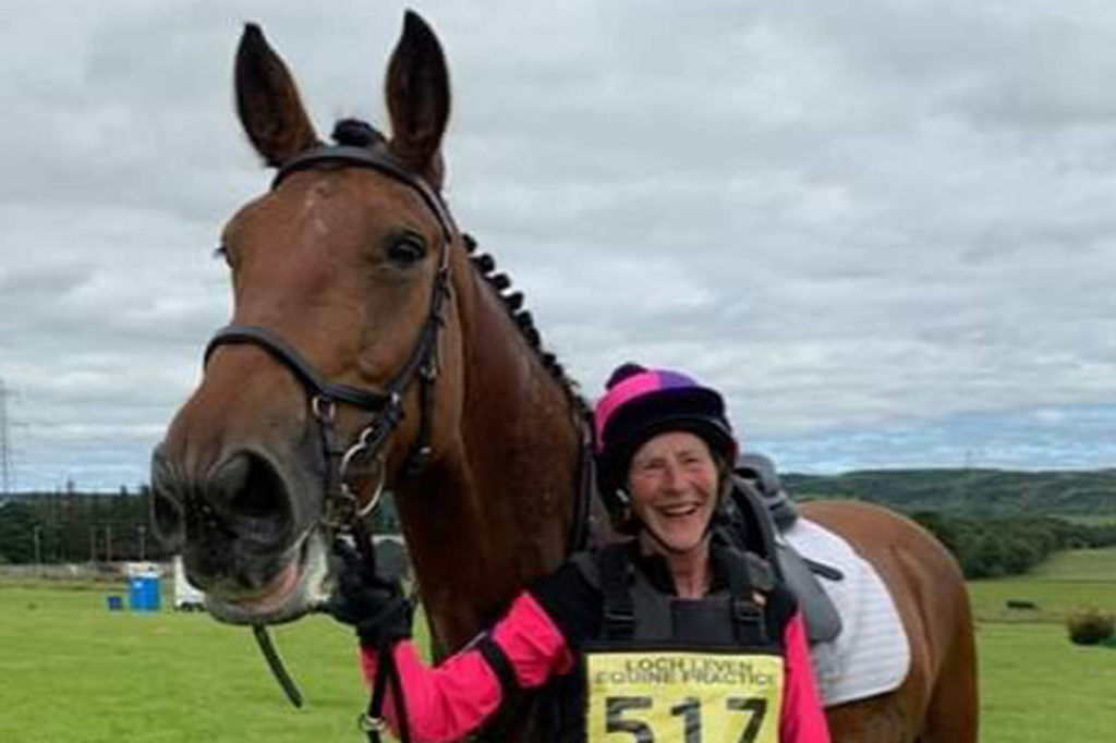 Bay horse wearing bridle and saddle held by his lady rider wearing cross country number and pink top