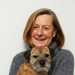 Lady wearing grey jumper and holding Border Terrier