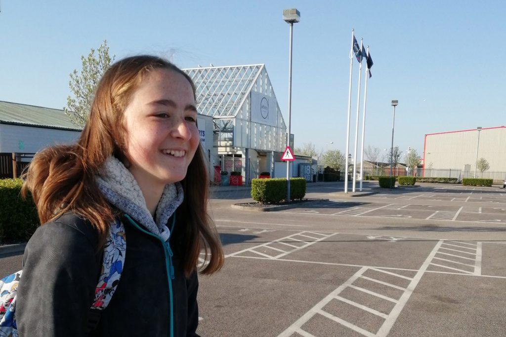 Girl in black coat in supermarket car park