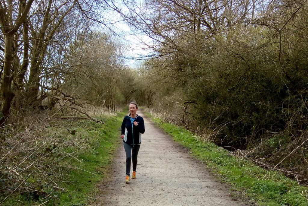 Woman running down a path between trees