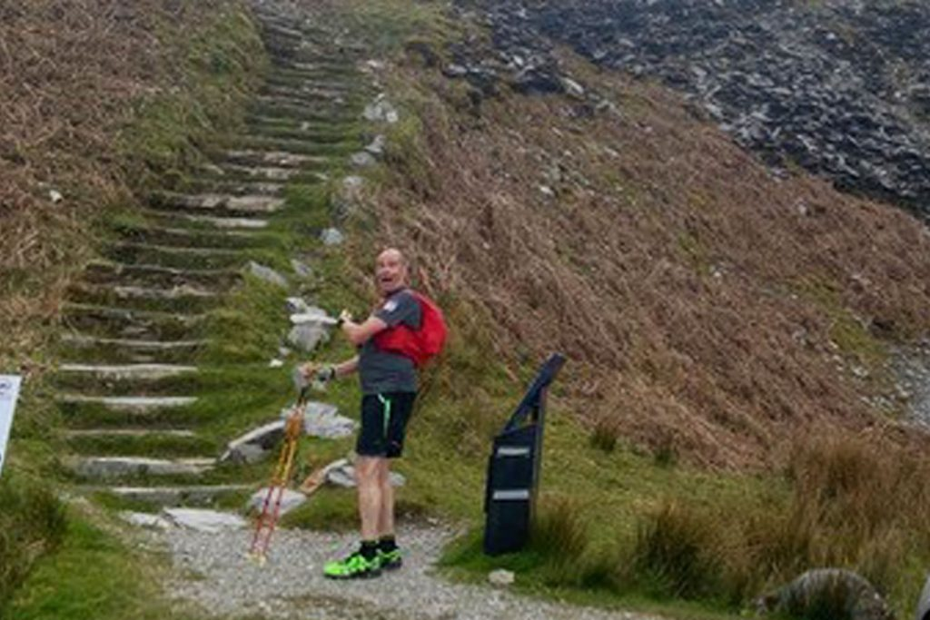 Runner stood at the bottom of a set of steps on a mountain