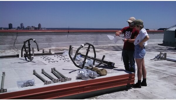 Student Media IT Manager Doug Flowers shows General Manager Emily Ehling pieces of the WKNC antenna on the roof of D.H. Hill Library. WKNC reconfigured its antenna pattern in June 2016 to reach further southeast toward Goldsboro and Wilmington. Photo by Jamie Lynn Gilbert.