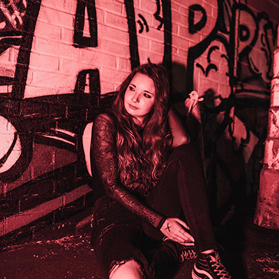 The Saw sitting against a graffitied wall surrounded in red light