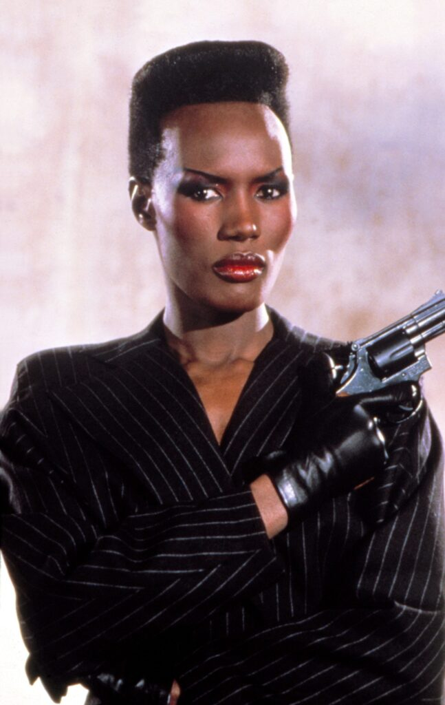 A black woman poses holding a revolver
