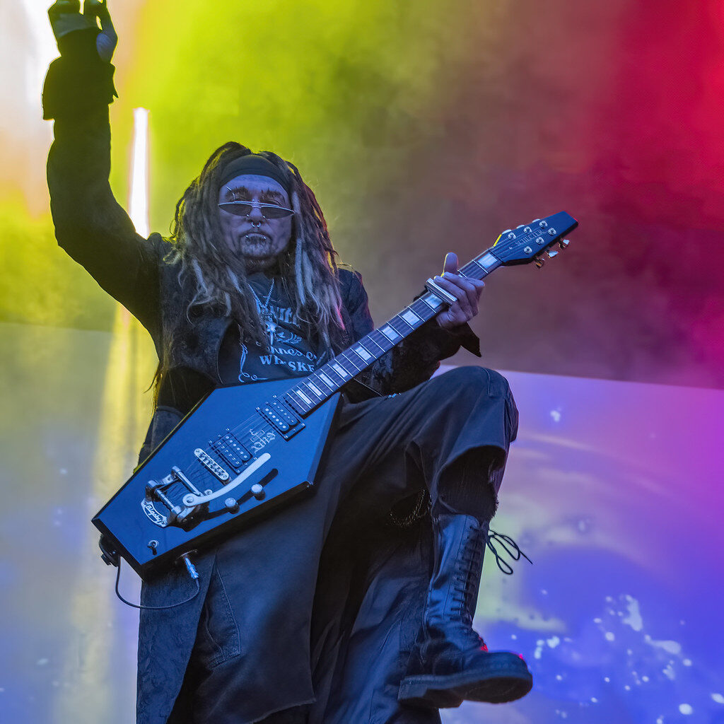A older man with dreadlocks plays a guitar