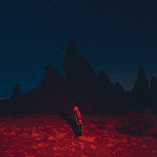 Alt text: Punisher's album cover depicts Phoebe Bridgers standing alone in the middle of the desert at night. The desert ground is covered in rocks and lit by bright red lighting. The rest of the landscape is dominated by dark mountain rocks and a dark blue night sky. Phoebe appears very small among the rocks at the bottom-center of the cover: she's standing straight, and you can see her from her right profile looking at the sky while her shadow is reflected on the ground.