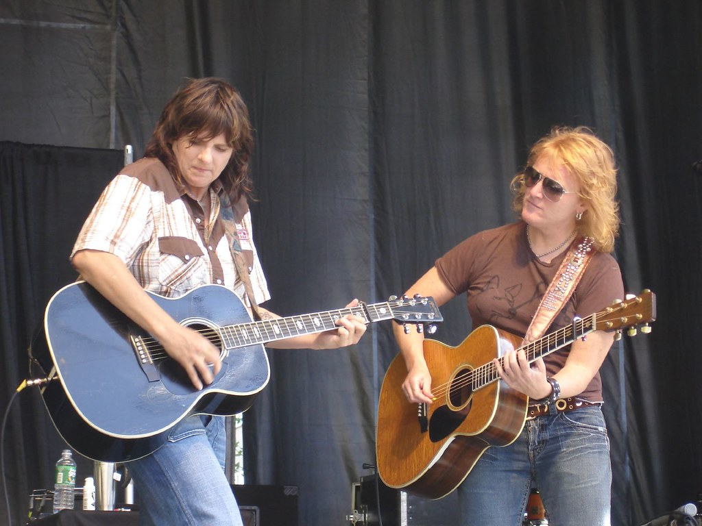 Two women in casual clothing play guitar on a stage