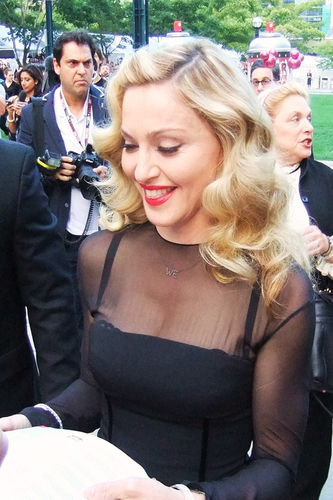 A woman in a black dress signs autographs