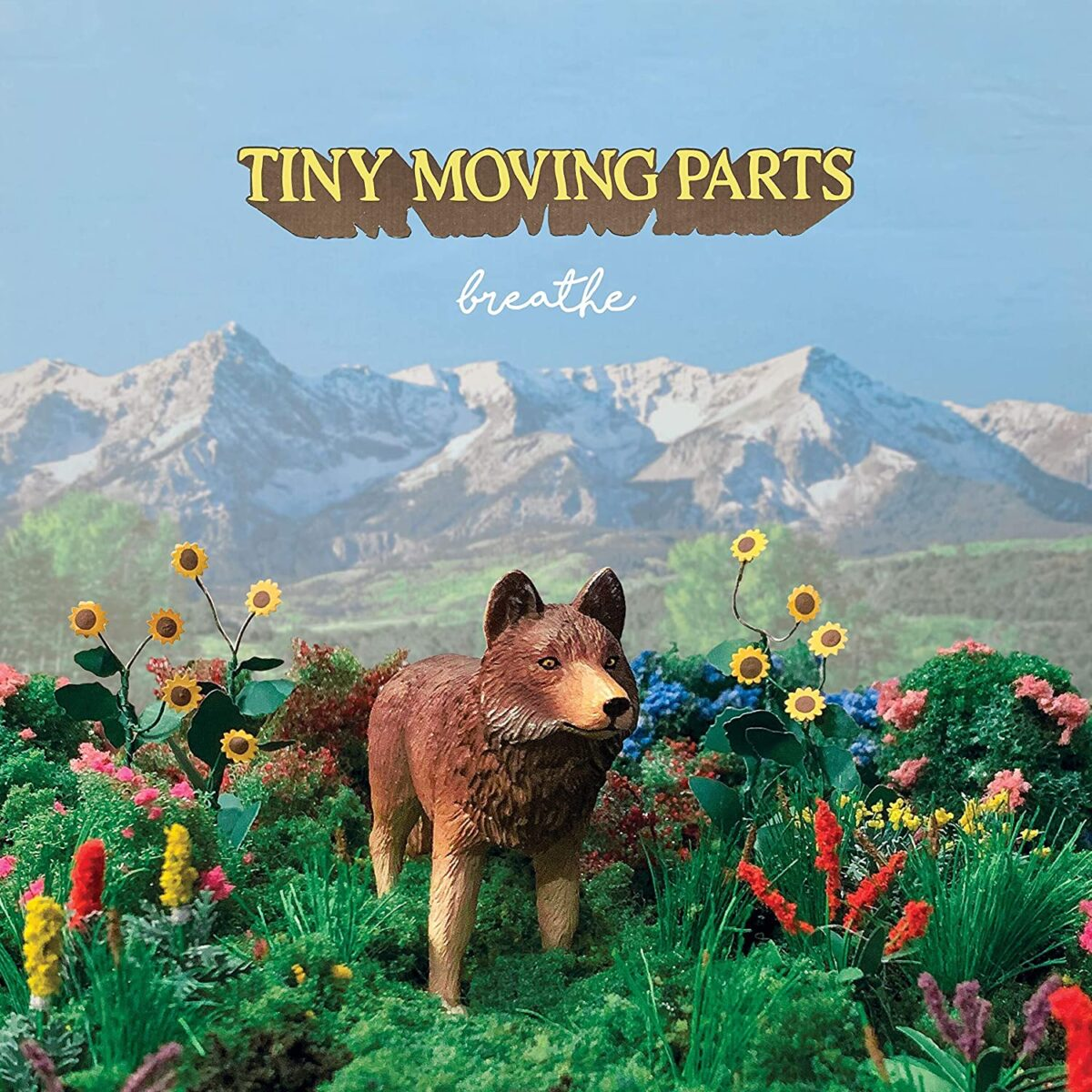 """""""breathe""""'s album cover depicts the painted statue of a wolf standing in the middle of nature, surrounded by red and yellow flowers. There are mountains and a big blue sky behind it and """"Tiny Moving Parts"""" is in yellow with brown outlines, in all caps."""
