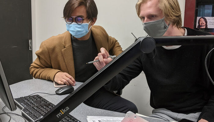 DJ Ethan Myers, right, shows trainee Curtis Cheung how to log songs on Spinitron.