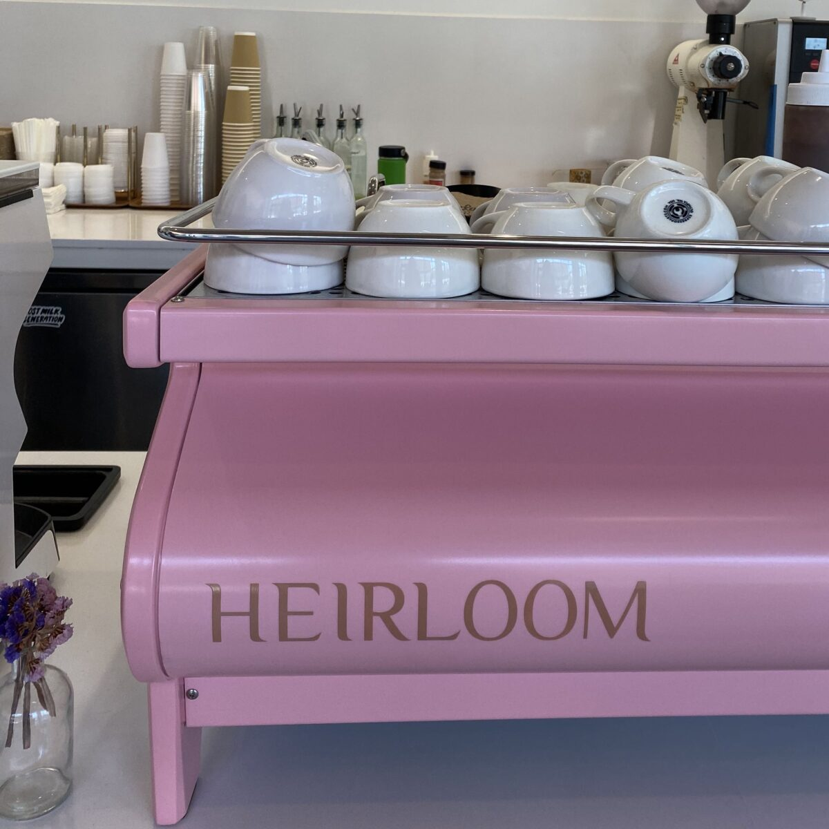 """This photograph features a pink coffee machine that says """"HEIRLOOM"""" in all caps, with white mugs sitting on it."""