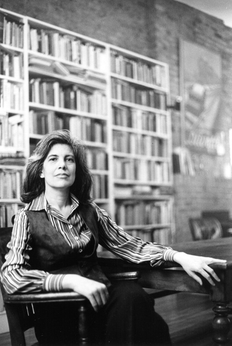 A black and white photo of Susan Sontag in front of a bookshelf