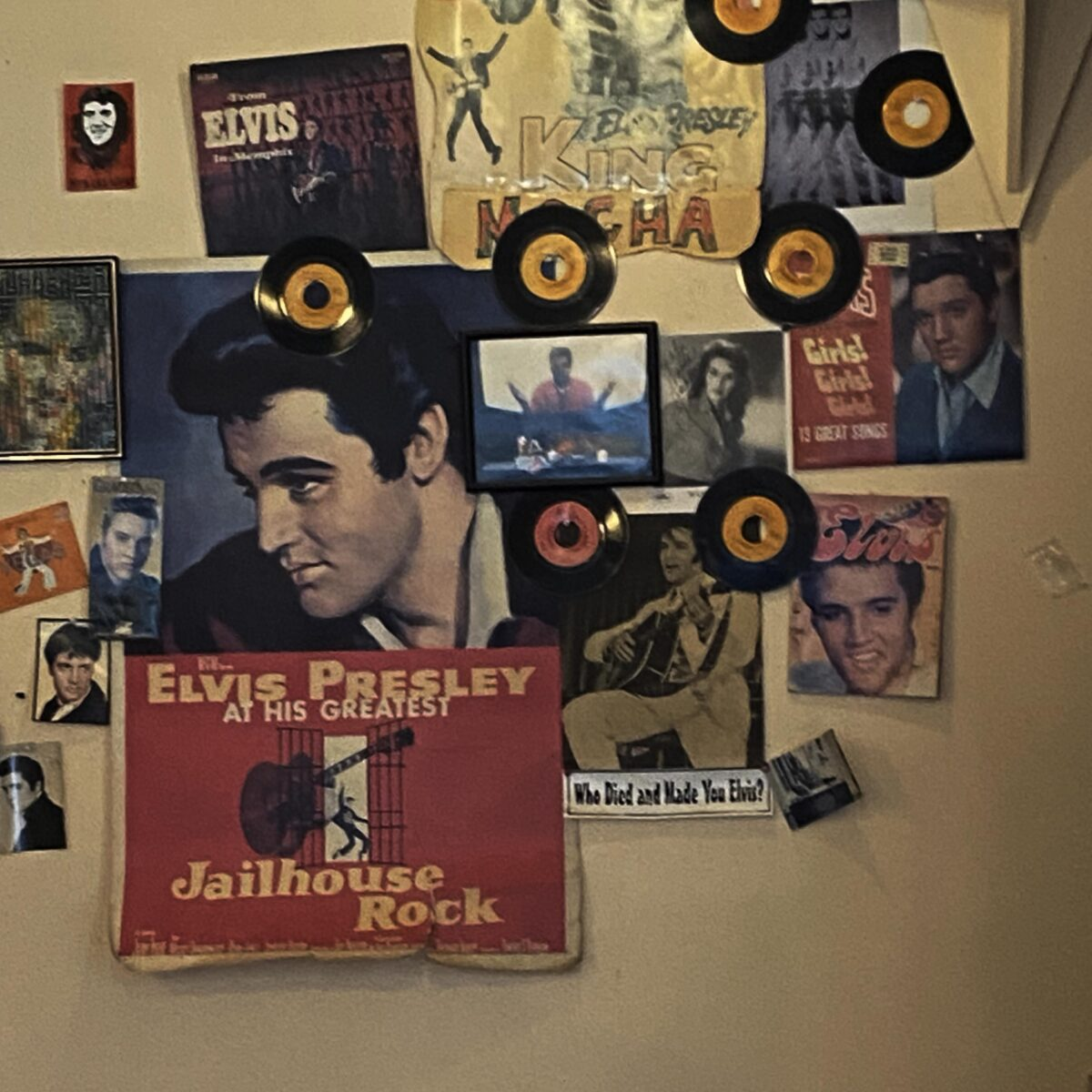 This photograph features a light brown wall at coffeeshop Cup A Joe in Raleigh, NC. The wall is covered with pictures of Elvis Presley and small orange and red vinyls.