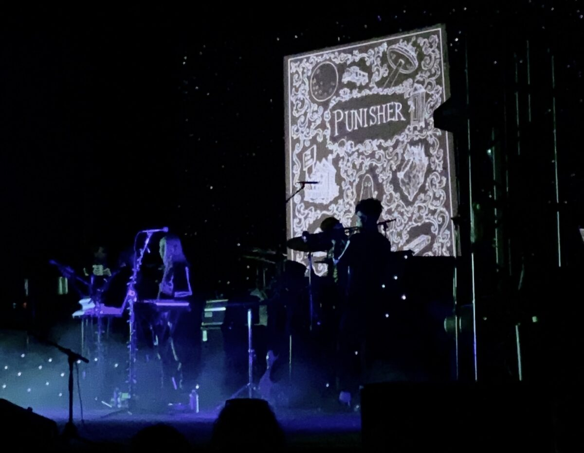 """Phoebe is on stage with her trumpetist. They're both wearing skeleton suits. A bright, blue light and smoke surround them. Behind them, a screen displays a black and white book cover that reads """"Punisher"""", with scary drawings decorating it."""