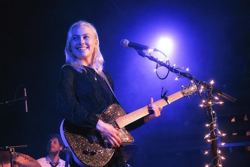 Phoebe bridgers with a purple background, performing, with a guitar in hand and smiling.