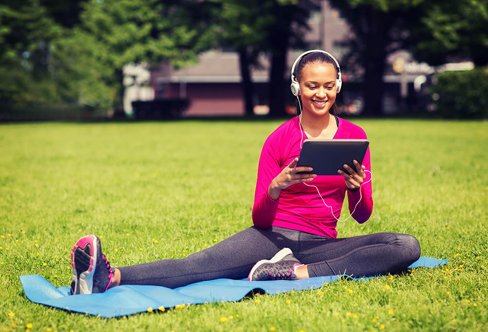 smiling woman with tablet pc outdoors