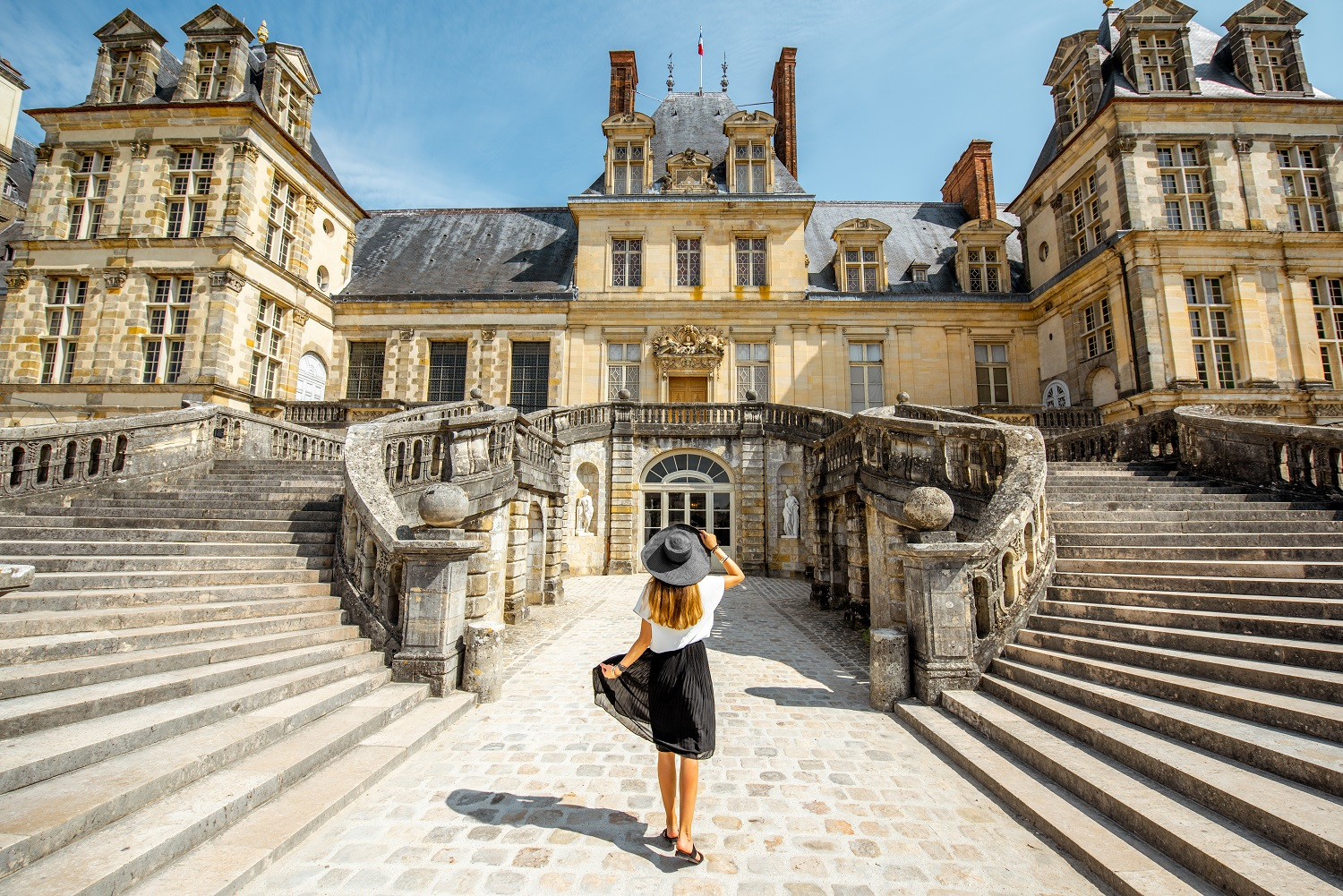 Woman standing back near the beautiful staircase visiting famous Fontainebleau palace in France