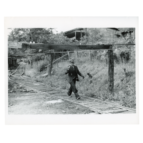 """Coal miner returning from work with pick over shoulder. The """"Patch,"""" Chaplin, West Virginia, Wolcott, Marion Post,"""