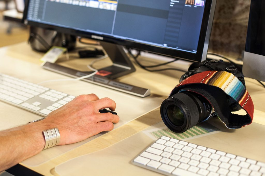 Close-up photograph of a camera and hands using a keyboard and mouse