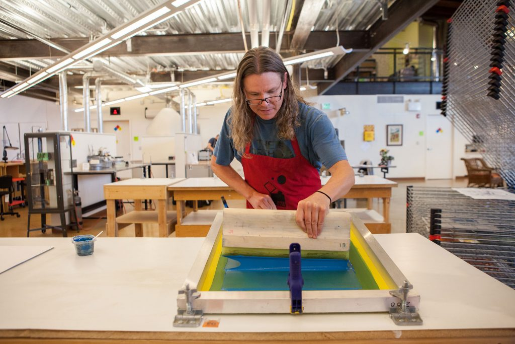 Photograph of Tyler Campbell screen printing with blue ink in in the screen printing workspace, with the metalsmithing workspace in the background