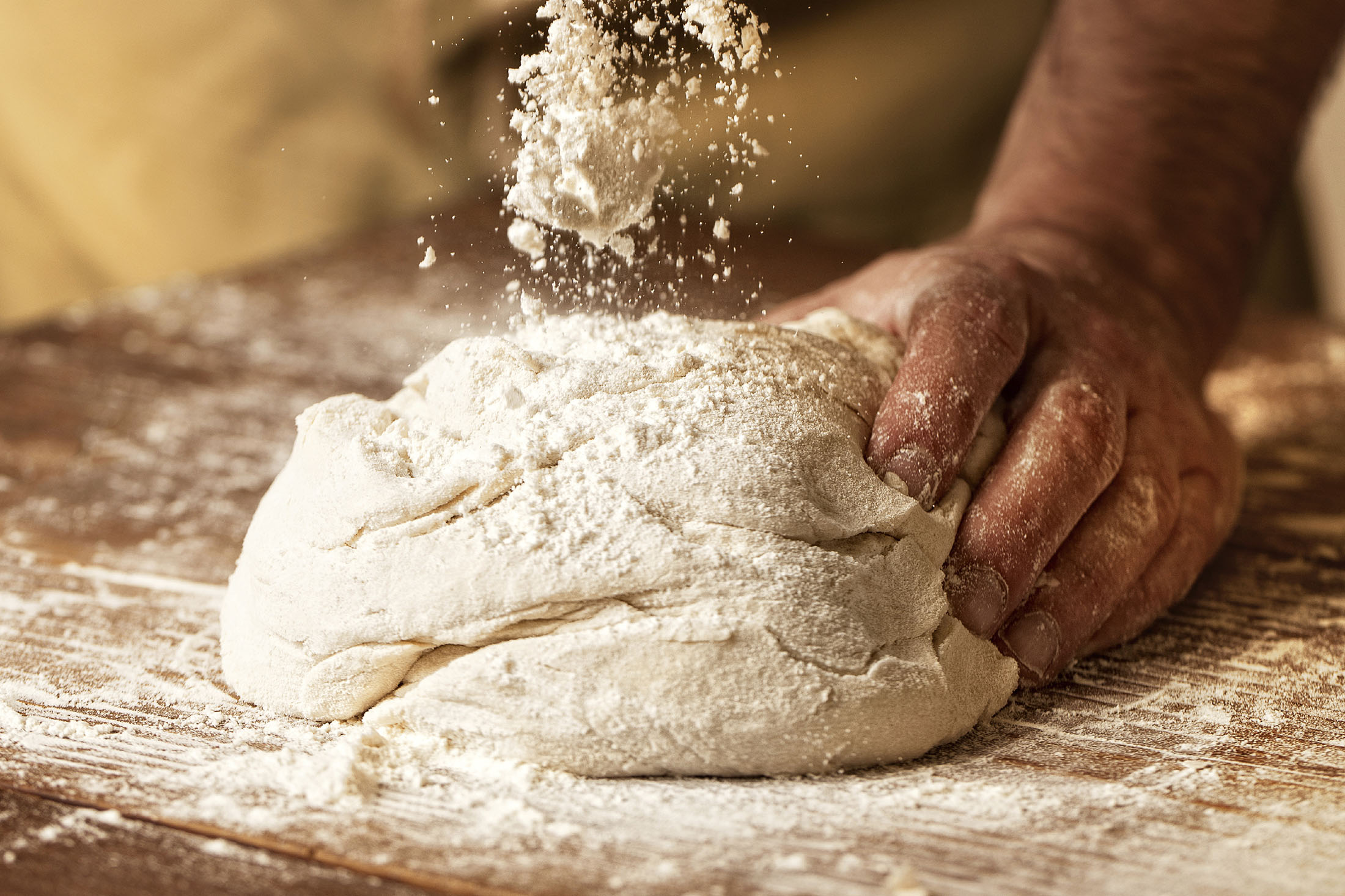 Close-up photograph of a hand kneading dough