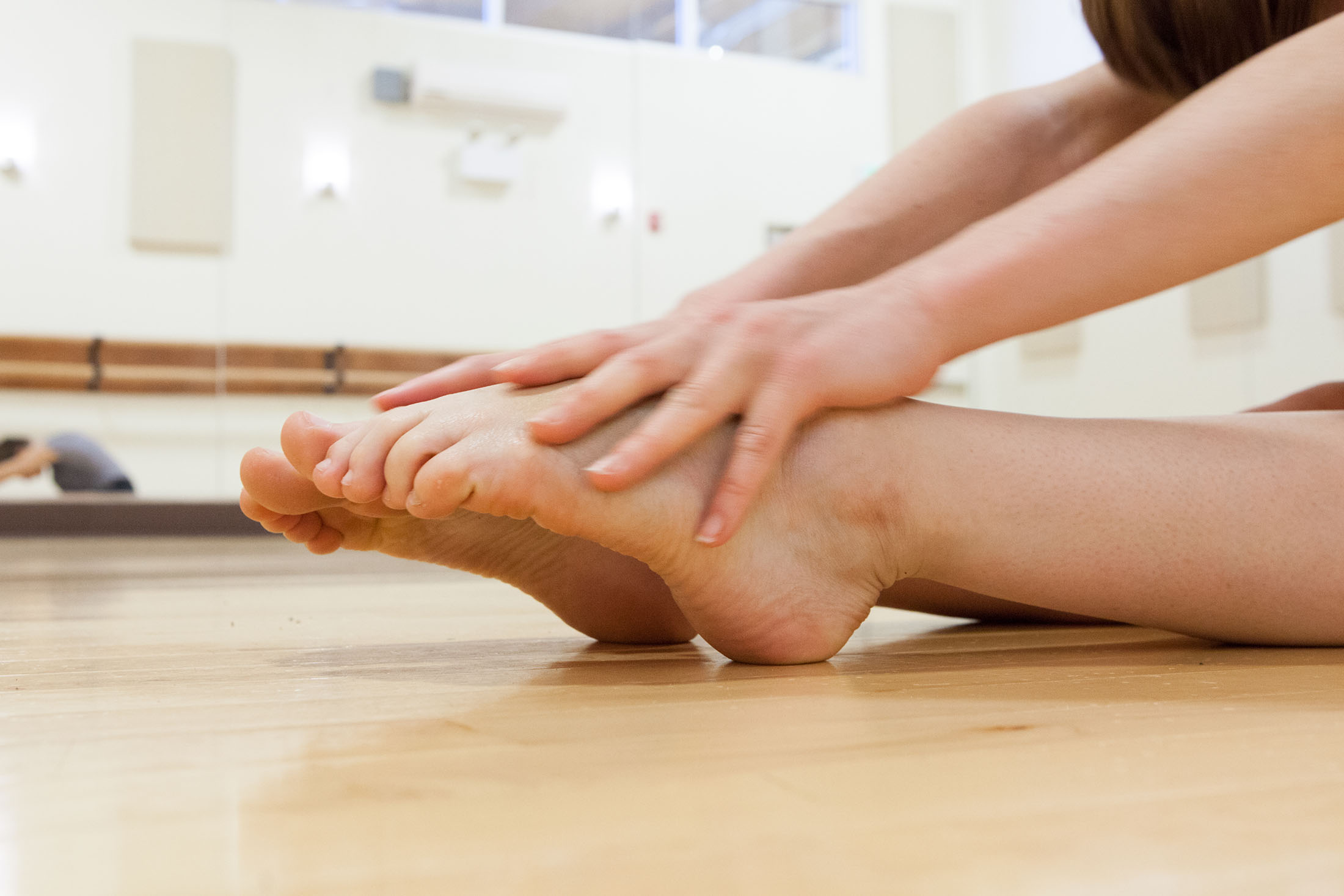 Close-up photograph of hands stretching out to bare feet in the performance workspace