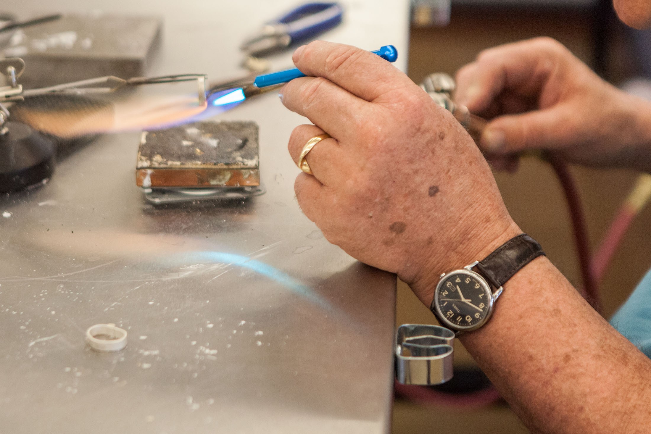 Close-up photograph of hands using an acetylene torch to solder a silver ring
