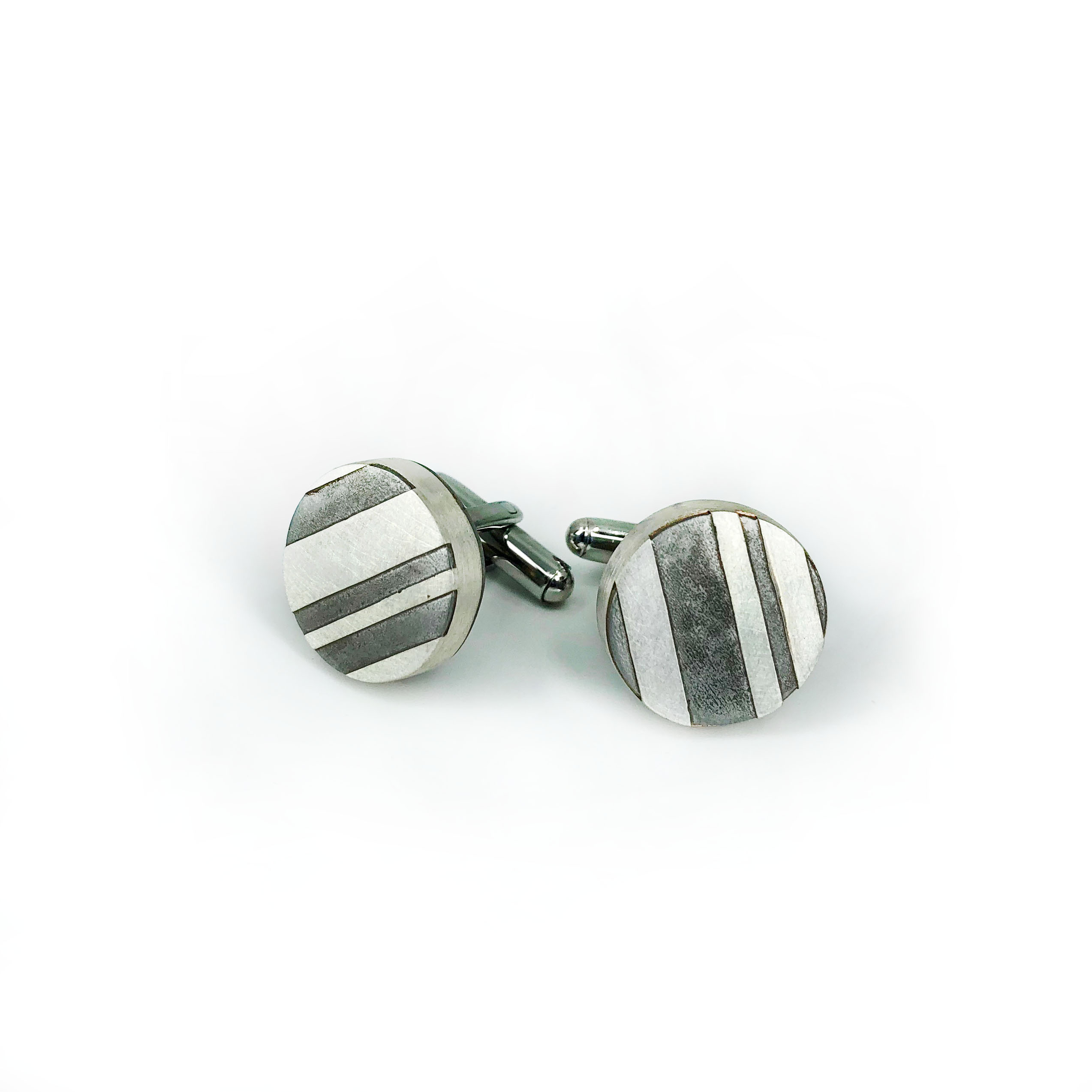 """Caitlin Zeller, """"Striped Cufflinks"""", hollow-formed - sterling silver and etched steel"""