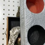 An assemblage of objects included a sculpture with recessed red and black circles