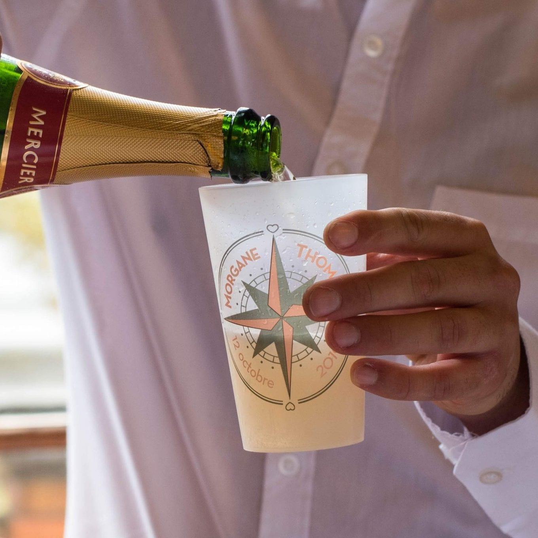 Un ecocup givré dans lequel un invité de mariage est en train de servir du champagne.