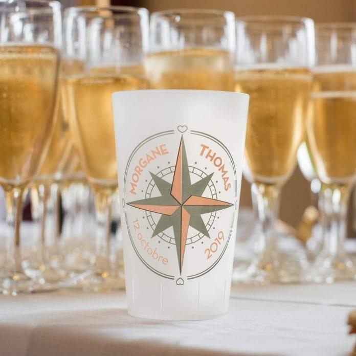 un ecocup givré de face personnalisé pour un mariage devant des coupes de champagne