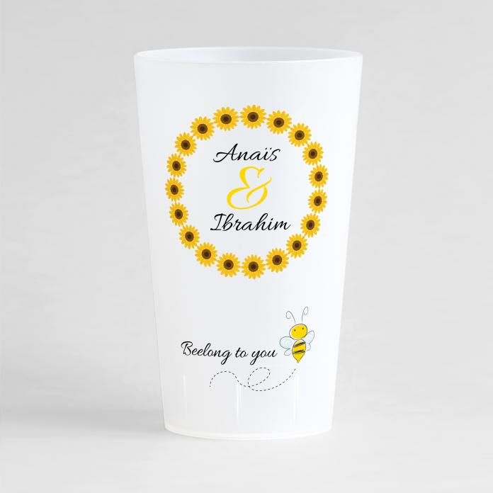 Un ecocup givré de face avec une couronne de tournesols autour des noms des mariés, et une phrase humour avec une abeille.