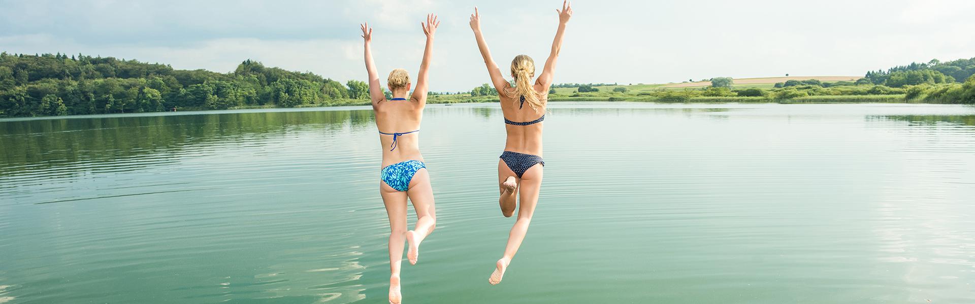 Zwei Freundinnen springen in einen See mit ihren Armen in der Luft